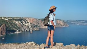 Back view successful backpacker travel woman admiring amazing sea landscape surrounded by mountain. Full shot. Active hiker female enjoying beautiful landscape stock video
