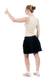 Back view of successful woman thumbs up. Rear view people collection. backside view of person. Isolated over white background. slender blonde in a dress shows Royalty Free Stock Photos