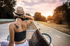 Back view tattooed hipster beautiful woman sitting on bench Royalty Free Stock Photo