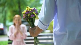 Back view of teen boy presenting bunch of flowers to girlfriend, surprise. Stock footage stock video
