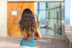 Back view of a teen girl walking towards the school. With the door in the background Stock Images