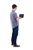 Back view of teenage boy holding laptop with blank screen isolat Stock Images