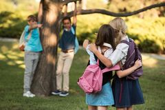 Schoolgirls with backpacks in park Royalty Free Stock Photos