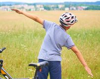 Back view of teenager boy in protective helmet spread his arms out like a bird standing next to his bike in park on royalty free stock photos