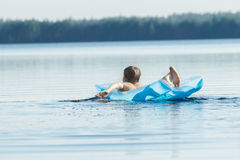 Back view of teenager paddling with his arms and floating on blue pool lilo outdoors Stock Images