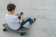 Back view.Teenager sits on skateboard,uses smartphone,digital gadget, plays computer games, browsing internet, chatting. Back view. Teenager, dressed in white t royalty free stock photo