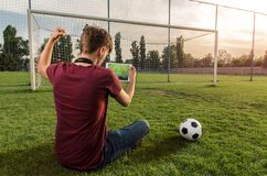 Back view, Teenager sitting on football/soccer field watching the game on tablet royalty free stock photos
