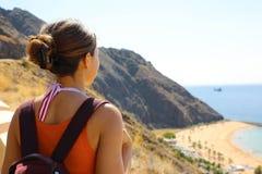 Back view from terrace of traveler girl looks to Playa de Las Teresitas seascape, Tenerife, Canary Islands.  stock photo