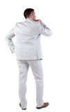 Back view of  thinking young business man in  white suit. Royalty Free Stock Photo