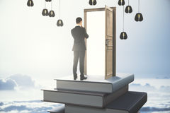 Career concept. Back view of thoughtful young businessman standing on abstract book tower with open door on sky background. Career concept. 3D Rendering Royalty Free Stock Images