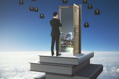 Knowledge concept. Back view of thoughtful young businessman standing on abstract book tower with open door on sky background. Knowledge concept. 3D Rendering Royalty Free Stock Photo