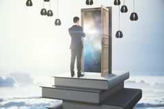 Leadership concept. Back view of thoughtful young businessman standing on abstract book tower with open door on sky background. Leadership concept. 3D Rendering Stock Photo