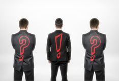 Back view of three businessmen with question mark and exclamation one in the center. Leader and leadership. Business concept and idea. To have your own opinion Stock Photography