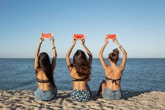 Back view of three dark-haired girls in jean shorts sitting on the sand near the sea holding watermelon slices over stock images