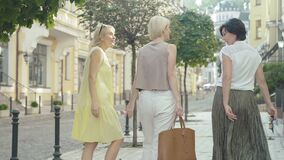 Back view of three excited women walking on town street and admiring buildings. Mid-adult elegant Caucasian tourists
