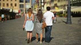 Back view of three friends drinking coffee and walking around the city. Two girls wearing sunglasses and short dresses. And handsome boy in white shirt and stock footage