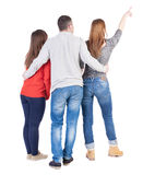 Back view of three friends pointing. Group of people watching somewhere. Rear view people collection.  backside view of person.  Isolated over white background Royalty Free Stock Photo