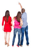 Back view of three friends. pointing man and two women looking. Back view of three friends. pointing men and two women looking. Rear view people collection Royalty Free Stock Images