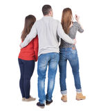 Back view of three friends  (woman and man). A guy in a gray jacket hugging two friends.  backside view of person.  Isolated over white background. Three Stock Images