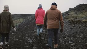 Back view of three people hiking in the mountains. Group of young people walking together, enjoying the Iceland. Man and two woman exploring the North nature stock footage