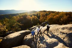 Guys with trial bicycles on the top of mountain at sunset stock photos