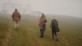 Back view of three young travelers hiking in the mountains valley in foggy day. Friends walking through the field. stock footage