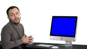 Casual businessman smiling and talking at the camera showing something on the monitor of computer, white background. Back view to the monitor of the computer stock photography
