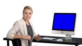 Young pretty lady talking to the camera and showing something on the screen of the computer, white background. Blue stock video footage