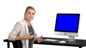 Young pretty lady talking to the camera and showing something on the screen of the computer, white background. Blue stock photography