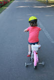 Back view of a toddler girl riding a bike, with helmet Stock Photo