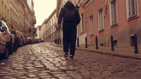 Man travelling in warsaw poland. Back view tourist with backpack walking in old city alone. unrecognizable guy going along parked cars on a narrow street stock video