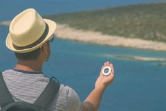 Hiker searching direction with compass near the sea shore. Back view of tourist guy with backpack holding and looking at compass for searching direction Royalty Free Stock Image