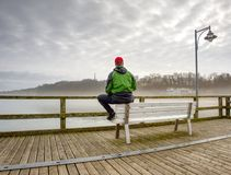 Back view of tourist in trekking clothes on sea wooden pier royalty free stock photos