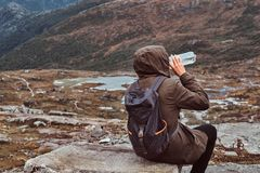Back view of a tourist who drinks water and sitting on a rock in the background of a beautiful mountain landscape. Back view of a tourist who drinks water and royalty free stock photos