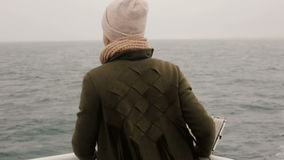 Back view of the tourist woman standing aboard a ferry and looking around. Female enjoying the view. Back view of the tourist woman standing aboard a ferry and stock video