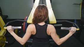A back view of a trained girl doing exercises. Training for back muscles stock video footage