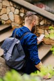 Traveler male with a backpack. Back view of the traveler male with a backpack stock image