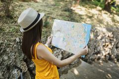 Back view Traveler tourist woman in yellow summer casual clothes, hat looking on city map, search route in city outdoor. Girl traveling abroad to travel on royalty free stock images