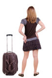 Back view of traveling blonde woman in dress with suitcase looki. Ng up. Standing young girl. Rear view people collection.  backside view of person. Isolated Royalty Free Stock Photography