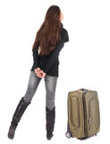 Back view of traveling brunette woman in jeans with suitcase loo. King up. Standing young girl. Rear view people collection.  backside view of person. Isolated Stock Photography