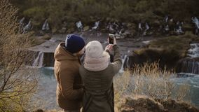 Back view of traveling couple standing near the waterfalls in Iceland on sunny day and taking selfie photo on smartphone. Tourists man and woman walking on stock video footage