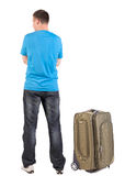 Back view of traveling man with suitcase looking up. Royalty Free Stock Photos