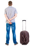 Back view of traveling man with suitcase looking up. Stock Image