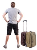 Back view of traveling man with suitcase looking up. Rear view people collection.  backside view of person.  Isolated over white background. Guy in shorts with Royalty Free Stock Photo