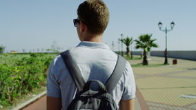 Back view of traveller walking on the street and looking at sights stock footage