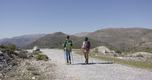 Back view of travellers in mountains. Back view of two young tourists backpacking in mountains and walking down road with trekking poles stock video footage