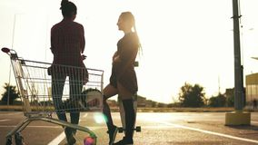 Back view of two attractive stylish girls standing by the shopping cart on parking and talking. One girl in shorts is stock video footage