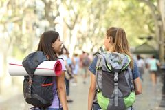 Back view of two backpackers walking in the street on vacation stock photo