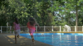 Back view of two barefoot little girls running along the swimming pool on a sunny day.  stock video