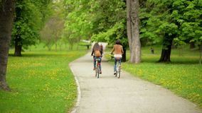 Back View of Two Brunettes with the Bicycles are Riding in the Park During the Spring. Funny Active Young Women in. Jackets and Jeans are Spending Time Outdoors stock video footage